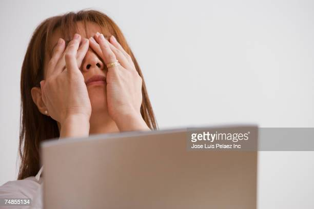 Asian woman rubbing eyes