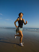 Asian woman running at beach