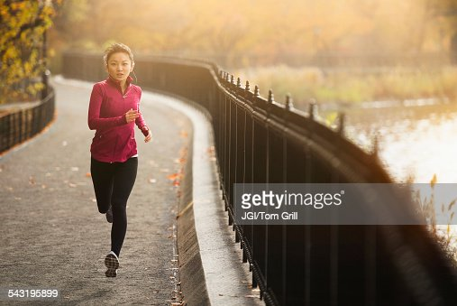 Asian woman running on waterfront path