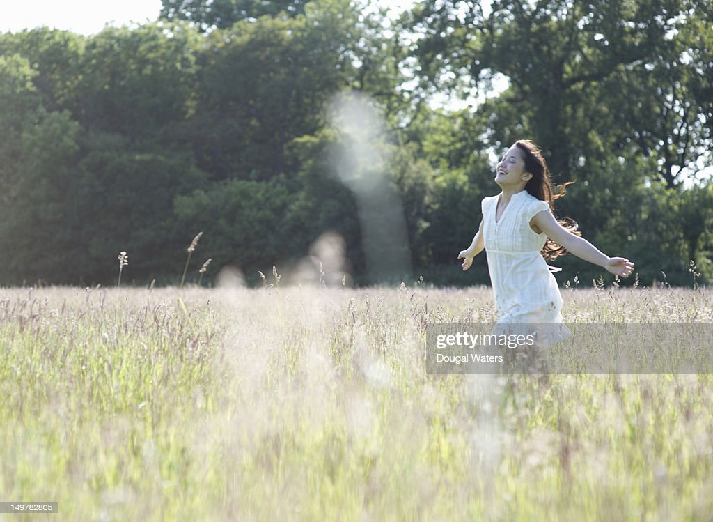 Asian woman running through meadow with arms out. : Stock Photo