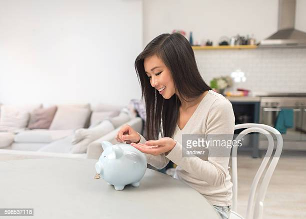 Asian woman saving money in a piggybank