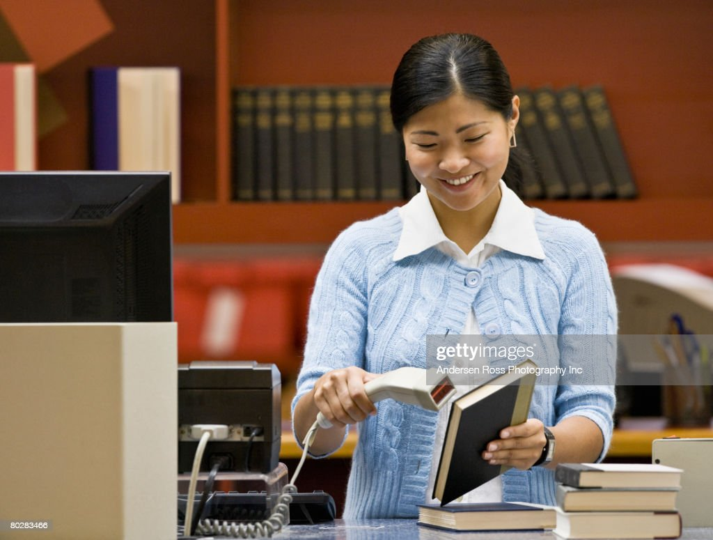 Asian woman scanning library book