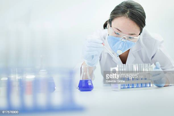 Asian woman scientist working with chemical in a laboratory.