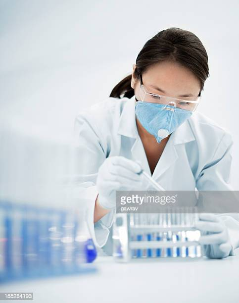 Asian woman scientist working with chemical wearing protective workwear