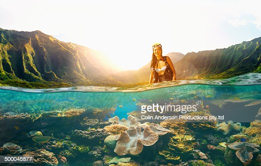 Asian woman scuba diving in tropical reef