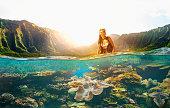 Asian woman scuba diving in tropical reef