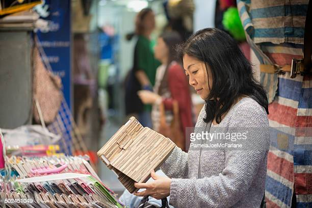 Asian Woman Shopping for Computer Tablet Case at Outdoor Market