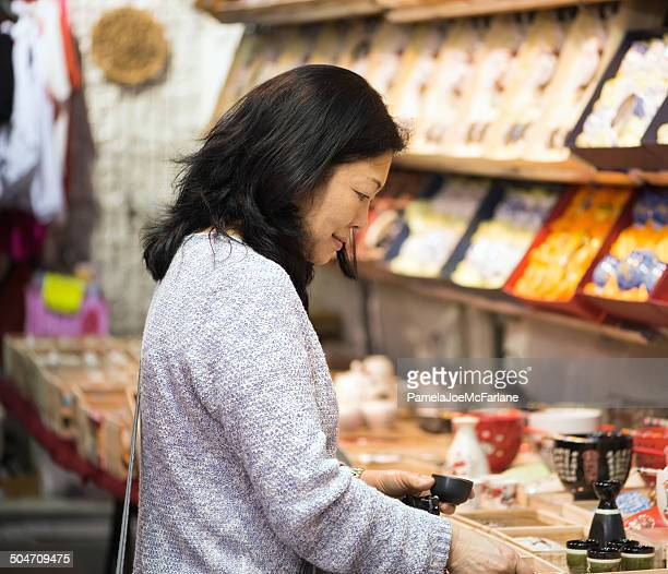 Asian Woman Shopping for Tea Set at Outdoor Market