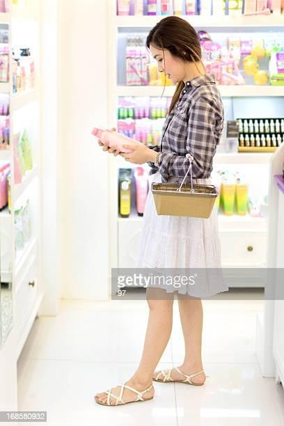 Asiatique femme shopping dans le magasin d'élaborer des produits cosmétiques.