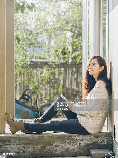 asian woman sitting at balcony with holding tablet pc
