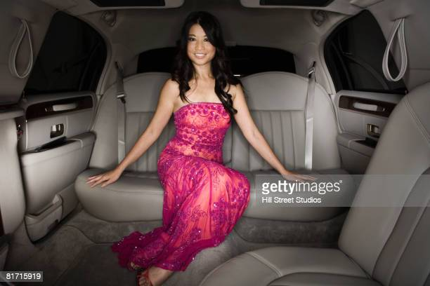 Asian woman sitting in limousine