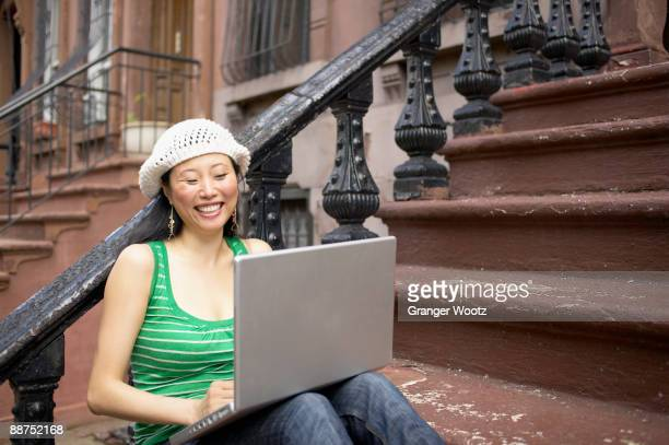 Asian woman sitting on front steps with laptop