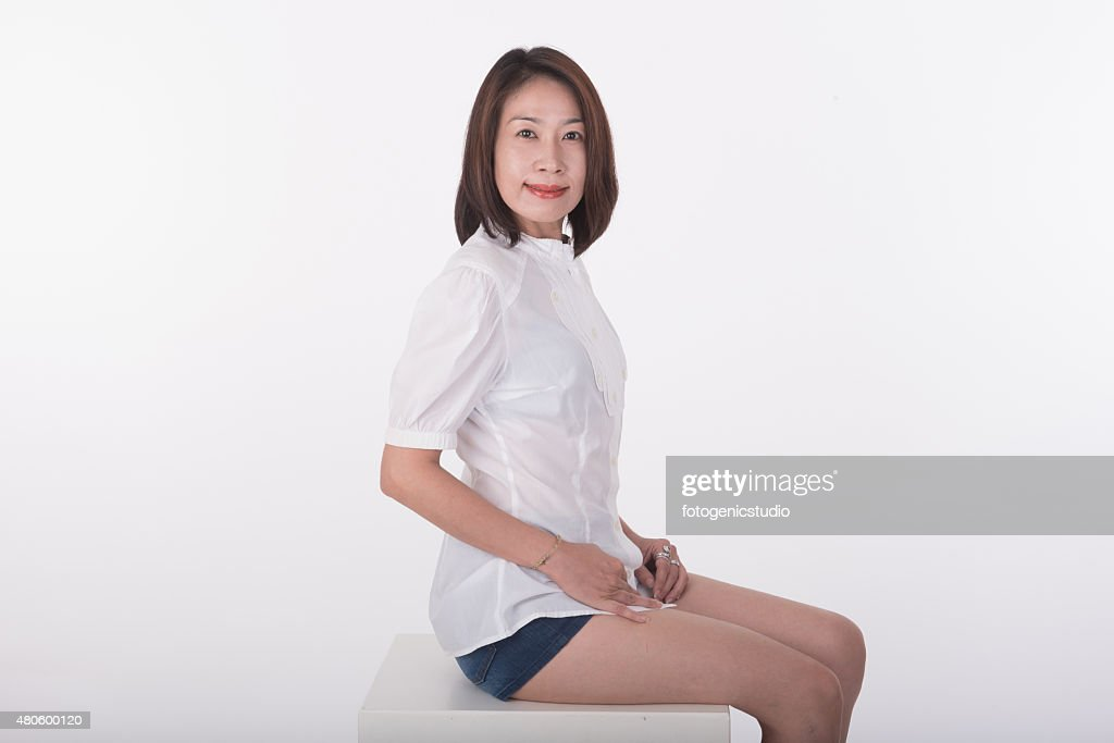 Asian woman sitting on white chair with white background : Stock Photo