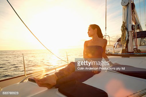 Asian woman sitting on yacht deck