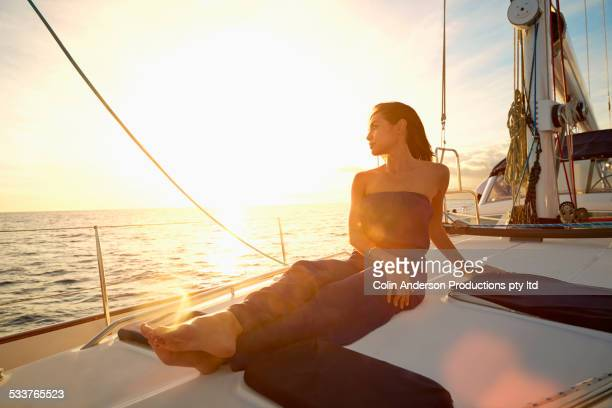 Asian woman sitting on yacht deck