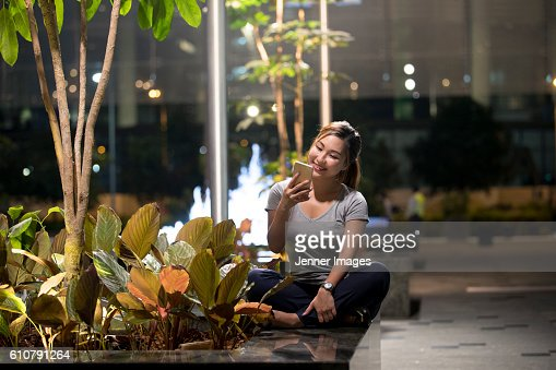 Asian woman sitting using her smart phone outdoors at night.