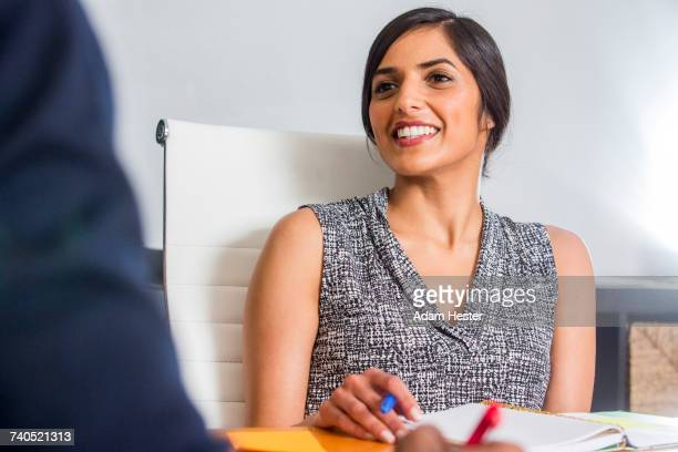 Asian woman smiling in business meeting