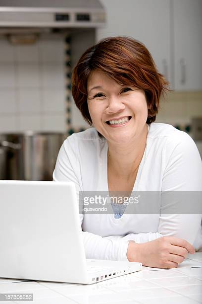 Asian Woman Smiling in Home Kitchen, Using Laptop, Copy Space