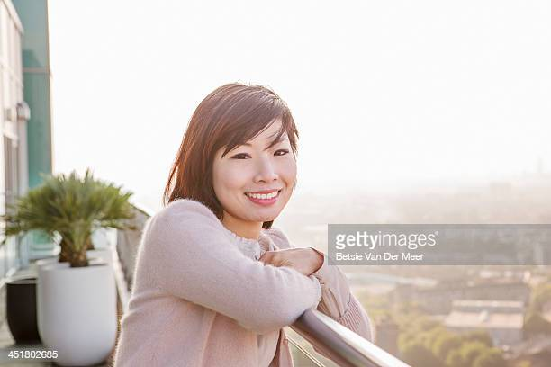 Asian woman smiling on balcony overlooking city.