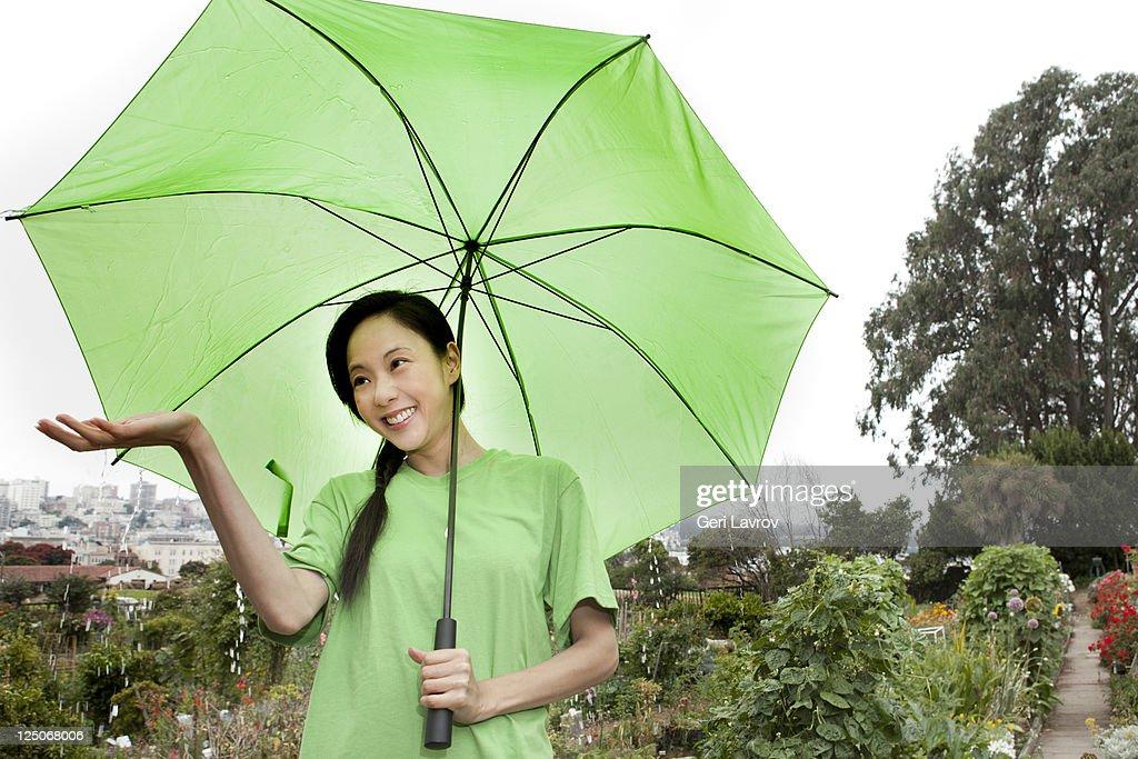 Asian woman standing in rain using umbrella : Stock Photo