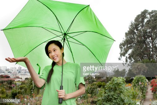 Asian woman standing in rain using umbrella : Bildbanksbilder