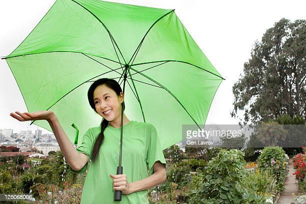 Asian woman standing in rain using umbrella
