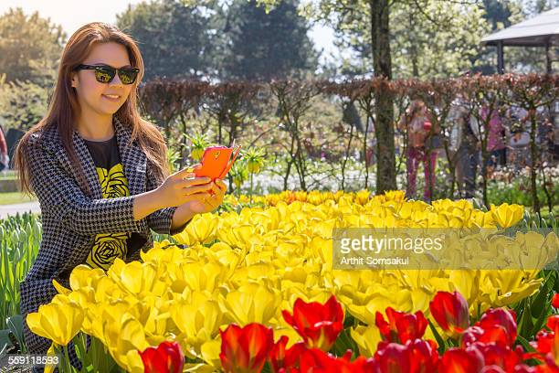 Asian woman take a picture of flower