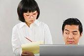 Asian woman taking notes next to man at computer