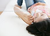 Asian woman talking by telephone and lying down on bed