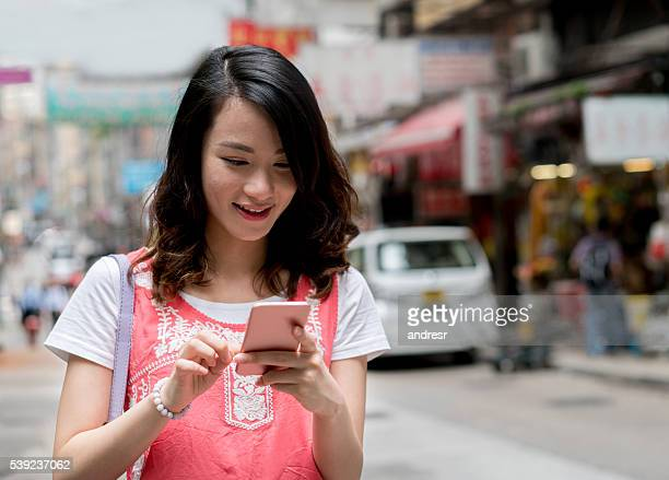 Asian woman text messaging in Hong Kong