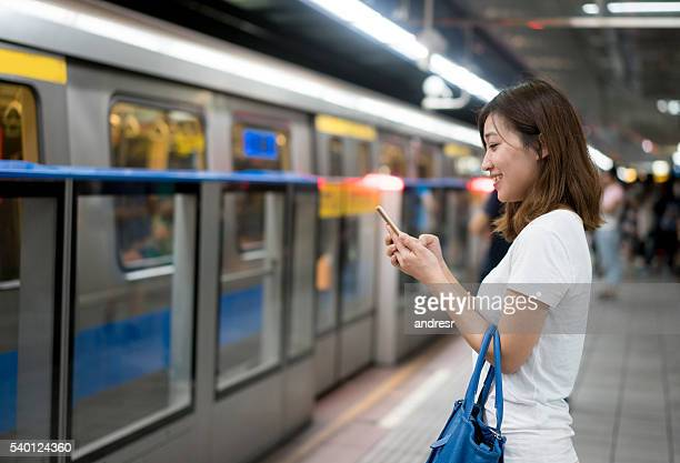 Asian woman texting at the metro station