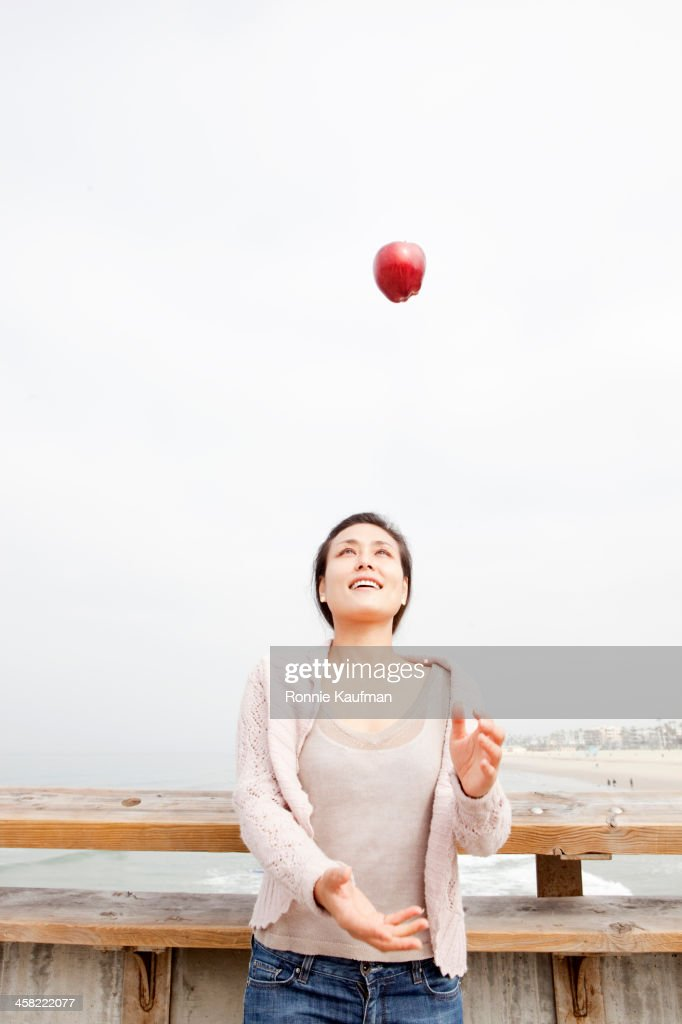 Asian woman throwing red apple