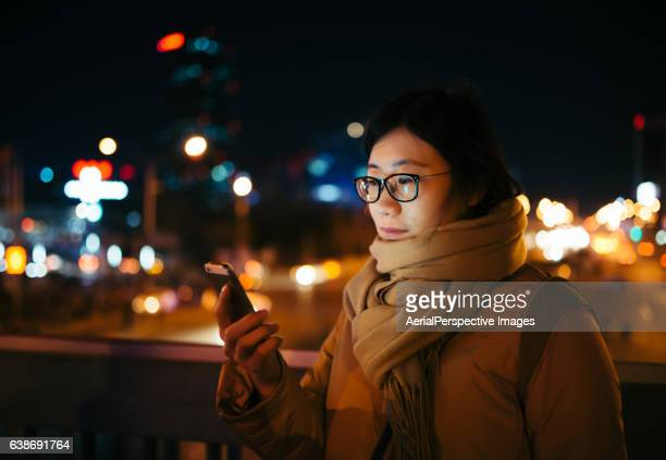 Asian Woman Using A Mobile Phone In Downtown District in Winter