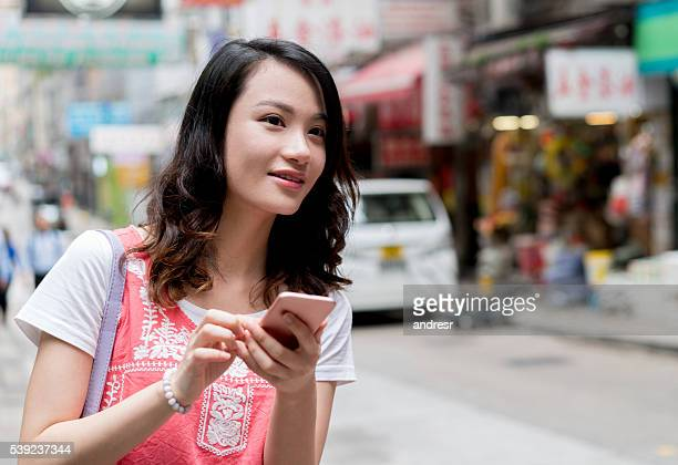 Asian woman using app to request a taxi
