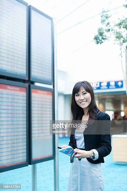 Asian Woman Using Cell Near Airport Arrival/Departure Board, Copy Space