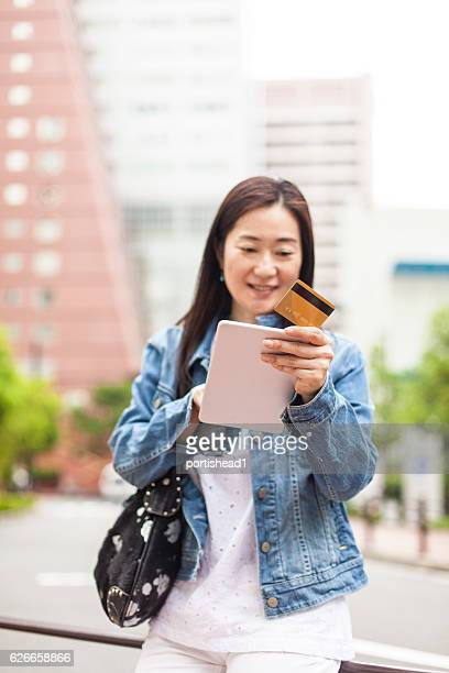 Asian woman using credit card for mobile payment