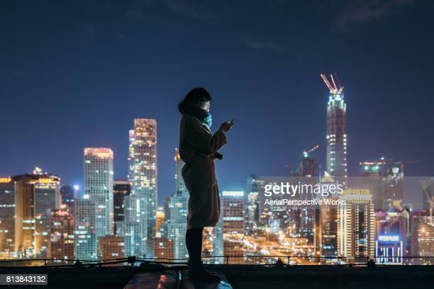 Asian Woman Using Mobile Phone In Downtown District