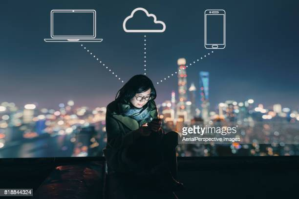 Asian Woman Using Mobile Phone on Rooftop