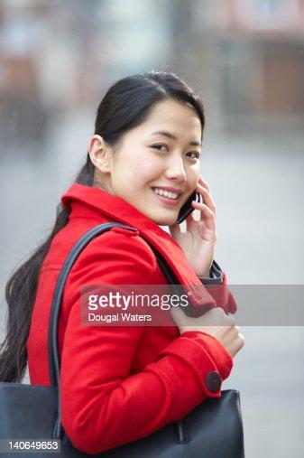 Asian woman using mobile phone.