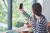 Asian woman using on mobile phone live on social media while drinking coffee near window at cafe restaurant,Digital age lifestyle,Technolgy using concept