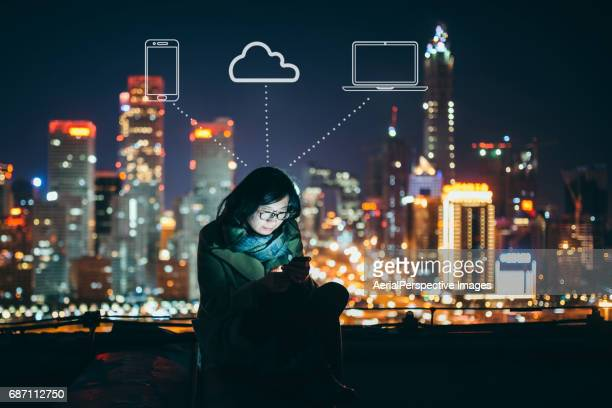 Asian Woman Using Smart Phone in Downtown at Night