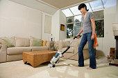 Asian woman vacuuming