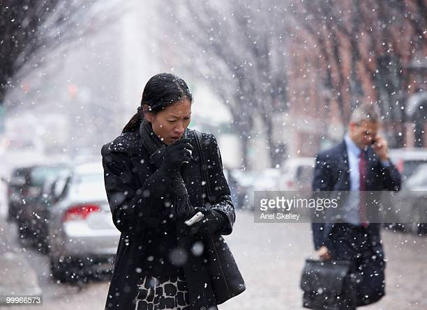 Asian woman walking in snow and coughing