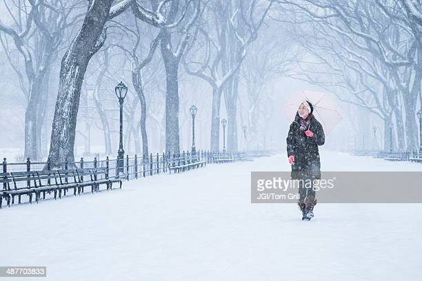 Asian woman walking in snowy park