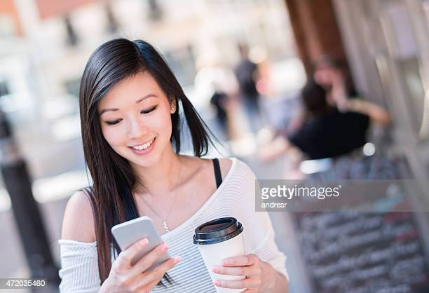 Asian woman walking on the street and texting