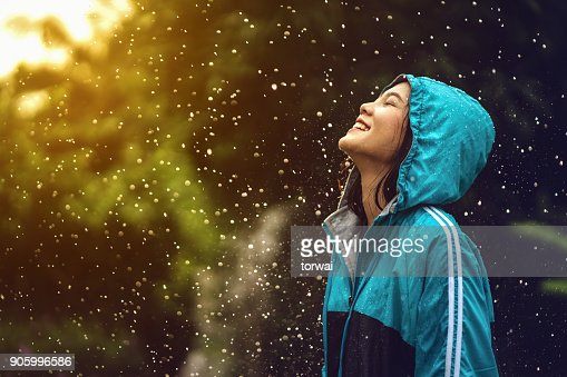 Asian woman wearing a raincoat outdoors. She is happy. : Foto stock