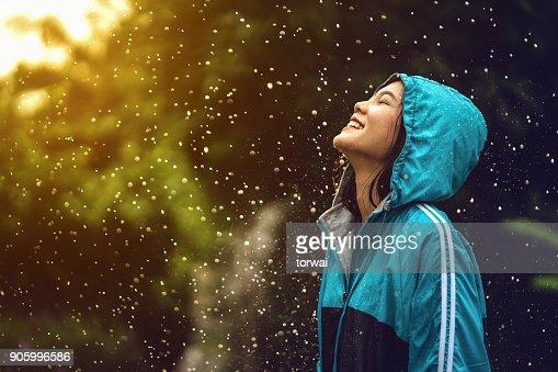 Mujer asiática con un impermeable al aire libre. Ella es feliz. : Foto de stock