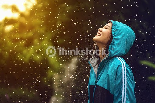 Asian woman wearing a raincoat outdoors. She is happy. : Stock Photo