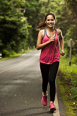 Asian woman were jogging on the road In the forest with sunny weather