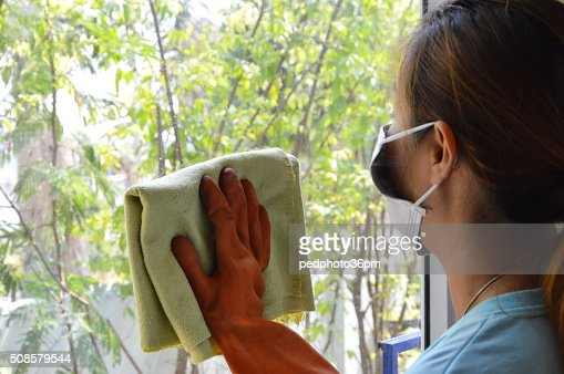 Asian woman wipe the glass in home : Stock Photo